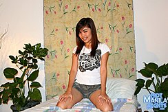 Kneeling On Bed Long Hair Down To Her White Tshirt Wearing Camo Shorts Hands Resting On Her Thighs