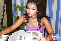 Long hair down over her bare shoulders wearing tight purple top writing notes holding book open
