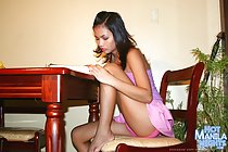 Medical student Yvonny  reading textbook at desk bare foot raised on chair