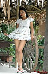 Leaning Against Wagon Wheel Pulling Hem Of White Dress In High Heels