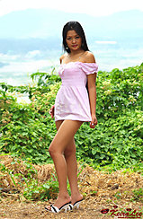 Standing On Hilltop Keira Lee Pulling The Hem Of Her Dress Down Wearing High Heels