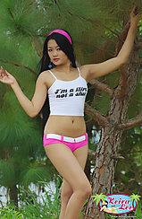 Standing Under Tree Arms Raised Wearing White Top And Pink Shorts Ribbon In Her Hair