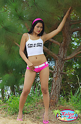 Under Tree Hand Raised To Branches Strappy White Top Hand On Her Pink Shorts In High Heels