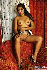Keira Lee Seated Naked On Chair Bare Breasts Long Hair Wearing High Heels Raising Skirt To Expose Her Shaved Pussy