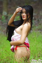 Standing in field pushing her long hair back from her face pert breast hard nipple wearing thong panties
