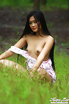 Sitting in field small breasts bared long hair hands on knees