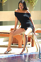 Keira Lee Beside Pool Wearing Black Dress Hand Resting On Her Thigh