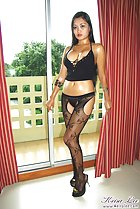 Curtains open at french windows Keira Lee wearing black lingerie in high heels