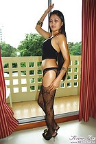 Overlooking balcony hand on her black stockings black high heeled shoes