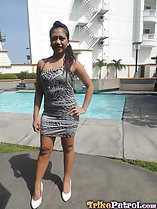 Cloe standing beside pool wearing dhort dress in while high heels hand on hip