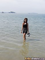 Wading in the sea holding her shoes