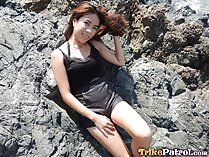 Chelsy seated on rock playing with her hair hand resting on her thigh
