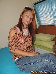 Sitting On Bed Long Hair Down Over Her Orange Top Wearing Jeans Legs Crossed