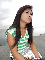 Seated on harbour wall long hair blowing in the breeze wearing striped top