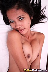 Zulaica Lying On Bed Long Hair Splayed Out Arms Pressing Her Breasts Together