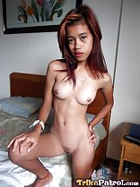 Bare foot raised on bed hand resting on knee hand on hip legs parted long hair down to her tiny tits