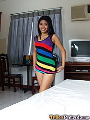 Wearing Colourful Striped Dress Long Hair Over Her Shoulder Pulling At The Hem Of Her Dress