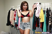 Standing between clothes racks wearing bra in denim shorts holding top