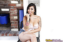 Brianna seated with her legs crossed big breasts